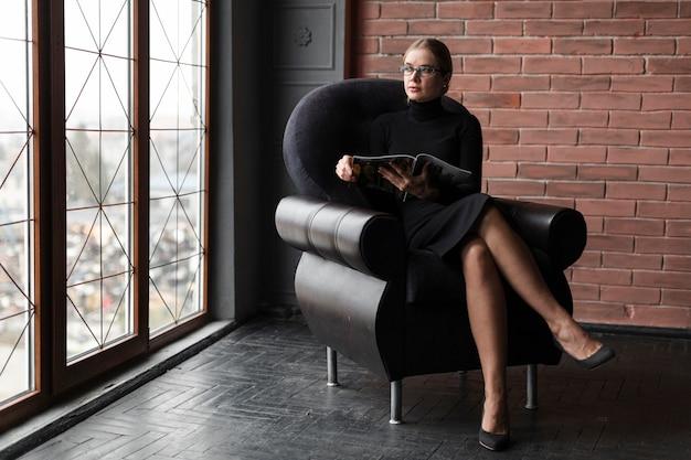 Mulher relaxando no sofá com a revista