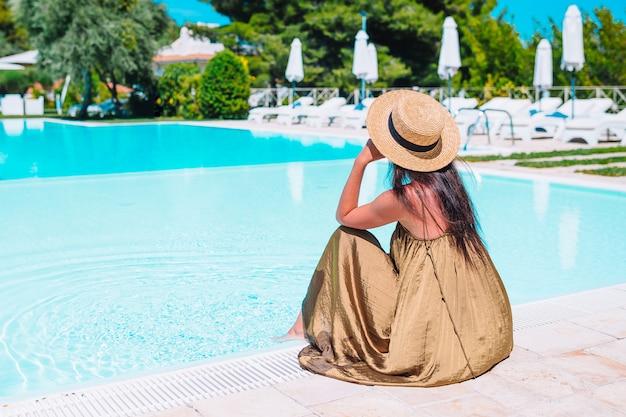 Mulher relaxante à beira da piscina em um resort de hotel de luxo, desfrutando de férias perfeitas férias na praia
