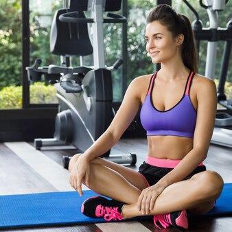 Mulher relaxante após seu treino no ginásio