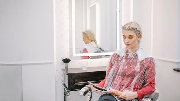 Mulher relaxante com revista de leitura de tintura aplicada