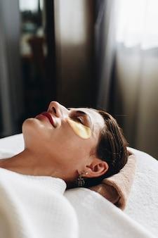 Mulher relaxante com um tratamento de máscara de olho dourado
