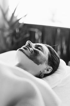 Mulher relaxante com uma máscara facial no spa