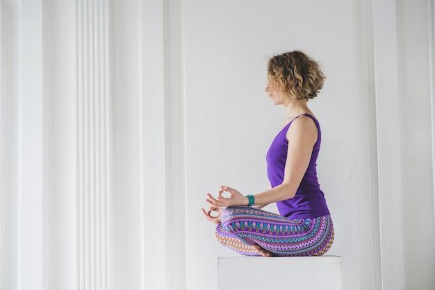 Mulher relaxante e meditando em casa