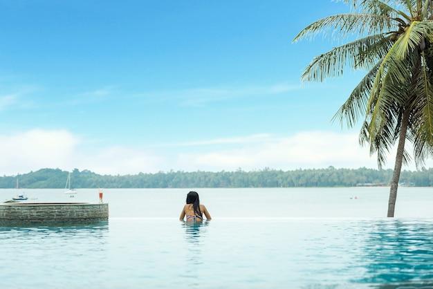 Mulher, relaxante, em, infinidade, piscina, olhar vista