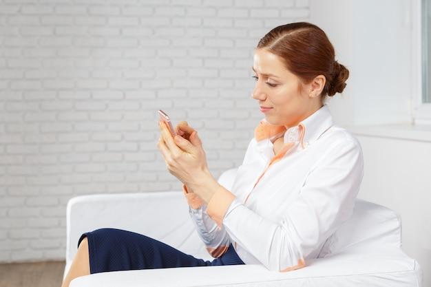 Mulher, relaxante, em, sofá, falando, ligado, mobilephone