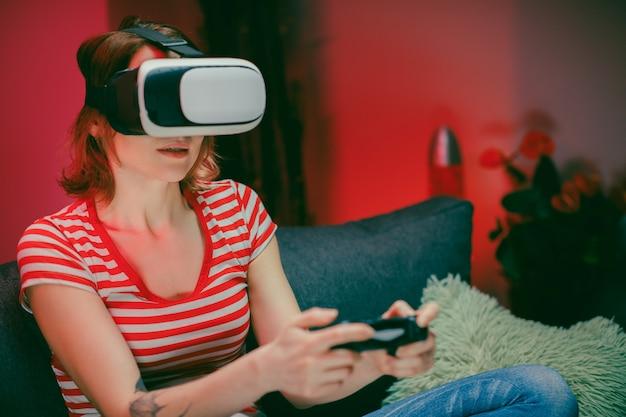 Mulher relaxante jogando videogame usando o fone de ouvido vr. jogador feminino caucasiano