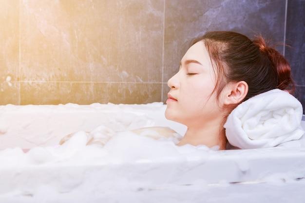 Mulher relaxante na banheira com os olhos fechados no banheiro