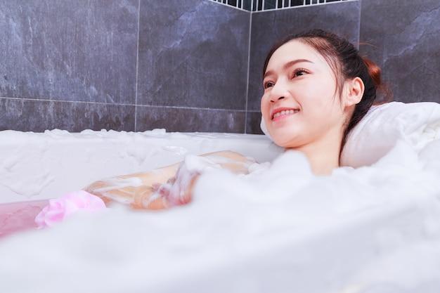 Mulher relaxante na banheira no banheiro