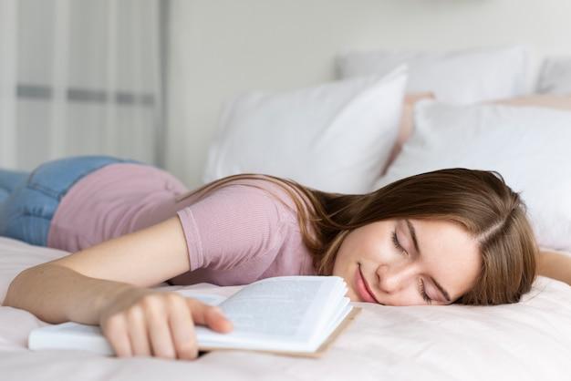 Mulher relaxante na cama com um livro