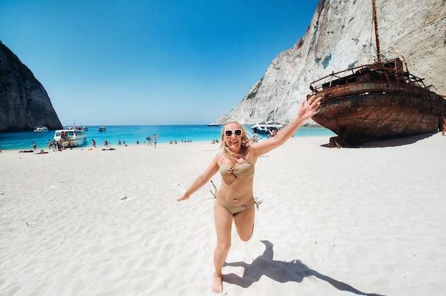 Mulher relaxante na famosa praia de navagio naufrágio em zakynthos, grécia.