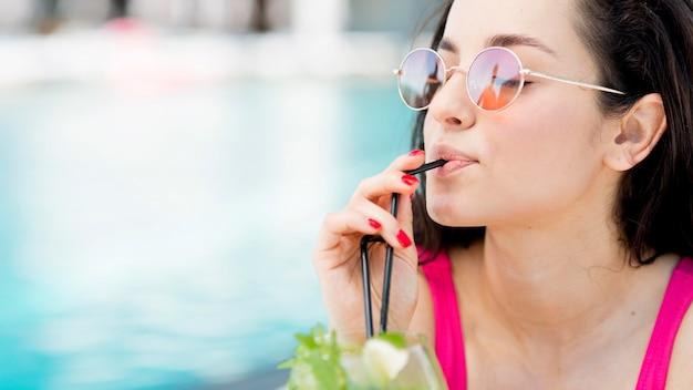 Mulher relaxante na piscina com uma bebida