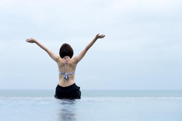 Mulher relaxante na piscina olhando a vista, conceito de viagens