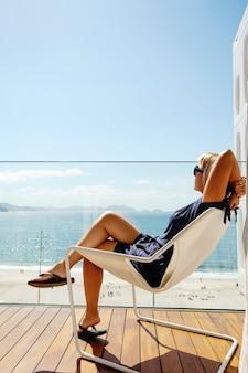 Mulher relaxante na varanda com vista para o oceano