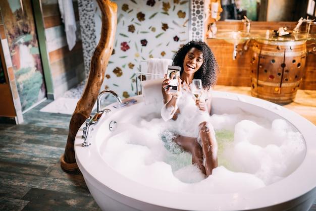 Mulher relaxante no banho de hidromassagem coberto de espuma com telefone celular