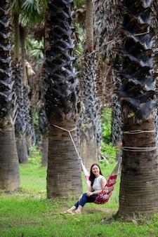 Mulher relaxante no jardim de palmeiras.