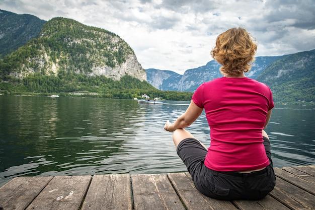 Mulher relaxante no lago no cais na bela paisagem com vista para montanhas, lago e céu azul