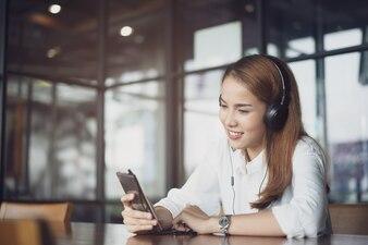 Mulher relaxante ouvindo música com fones de ouvido e smartphone.