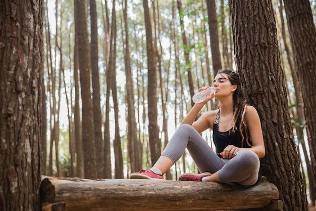 Mulher relaxante tomando uma garrafa de água
