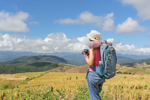 Mulher relaxante, viagem nas montanhas e aproveitando o tempo