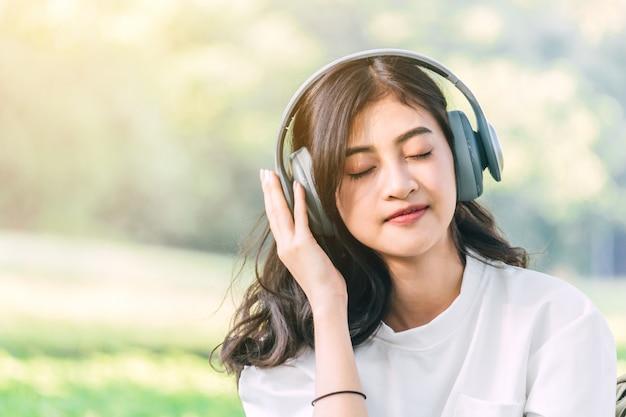 Mulher relaxar com fones de ouvido, ouvindo música, sentado na grama no parque