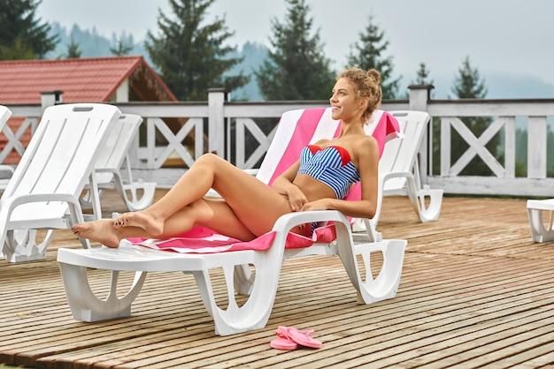 Mulher relaxar perto da piscina, tomando banho de sol no terraço.