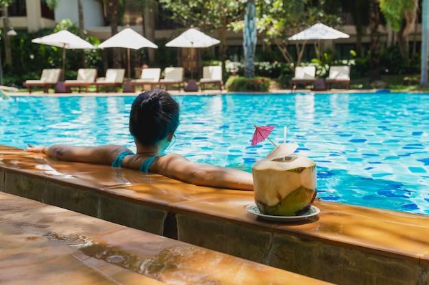 Mulher, relaxe, tendo, coco, bebida, e, escute música, em, piscina