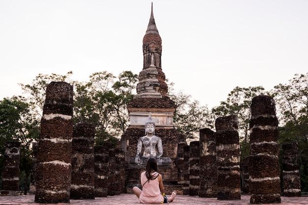 Mulher religiosa que visita os restos no parque nacional de sukhothai, a cidade antiga com herança budista na tailândia.
