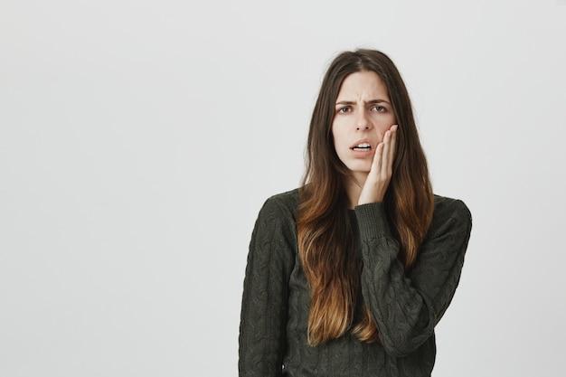 Mulher relutante irritada sendo incomodada, sentir-se exausta, tocar a bochecha e franzir a testa