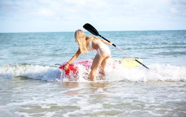 Mulher remando um caiaque na praia tropical. passeio de caiaque em phuket, tailândia