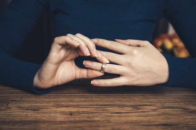 Mulher remove a aliança de casamento na mesa de madeira