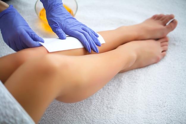 Mulher remove cera com pelos das pernas.