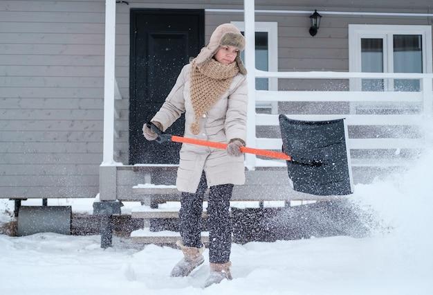 Mulher remove neve perto de uma casa de madeira