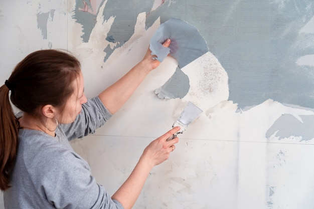 Mulher remove o papel de parede da parede com uma espátula