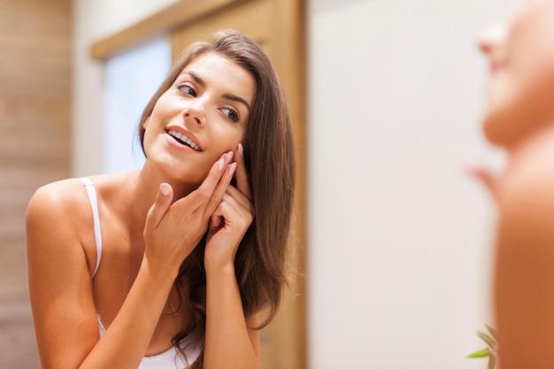 Mulher removendo espinha do rosto