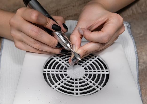 Mulher removendo goma-laca de unhas usando uma máquina de manicure