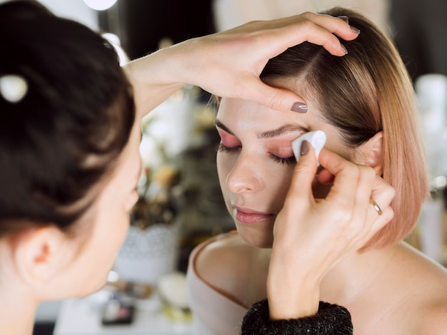 Mulher removendo maquiagem dos olhos do modelo