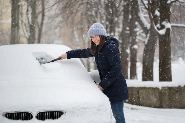 Mulher removendo neve do para-brisa do carro
