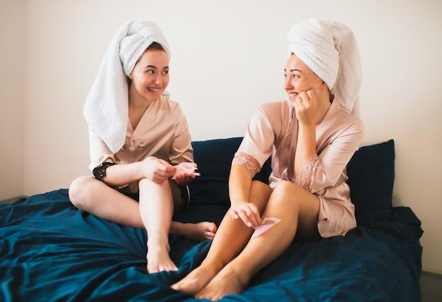 Mulher remover pêlos indesejados nas pernas com tiras de cera