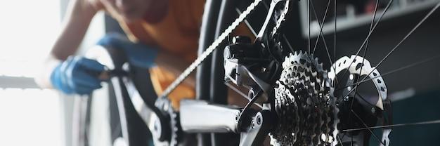 Mulher reparadora com luvas de borracha, consertando bicicleta com ferramentas closeup