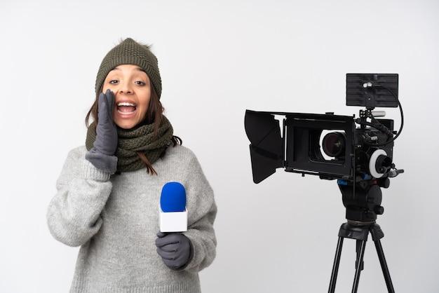Mulher repórter segurando um microfone e relatando notícias sobre um fundo branco isolado gritando com a boca bem aberta