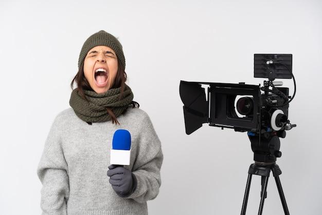 Mulher repórter segurando um microfone e relatando notícias sobre um fundo branco isolado gritando para a frente com a boca bem aberta