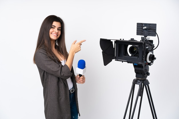 Mulher repórter segurando um microfone e relatando notícias sobre uma parede branca isolada apontando o dedo para o lado