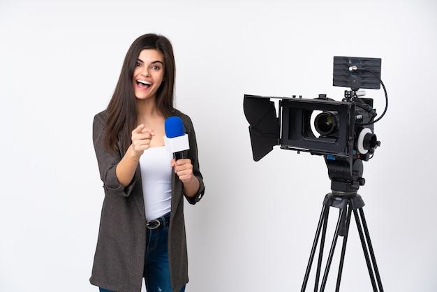 Mulher repórter segurando um microfone e relatando notícias sobre uma parede branca isolada apontando o dedo para você