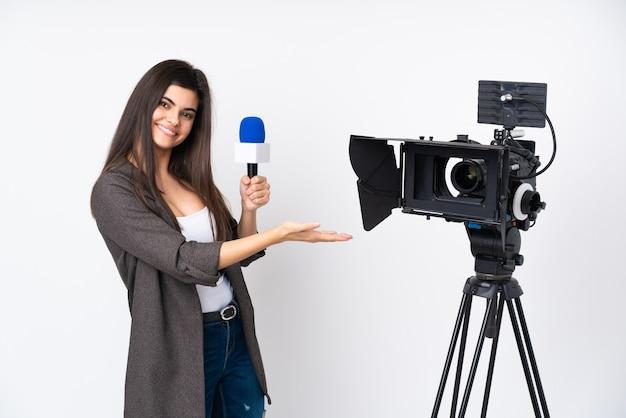 Mulher repórter segurando um microfone e relatando notícias sobre uma parede branca isolada, estendendo as mãos para o lado para convidar para vir
