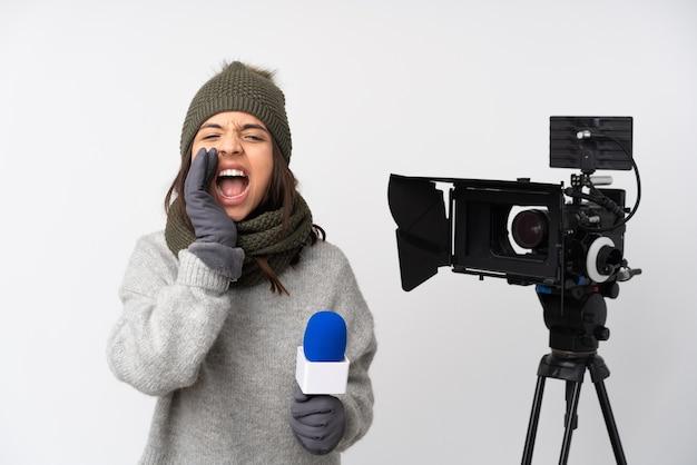 Mulher repórter segurando um microfone e relatando notícias sobre uma parede branca isolada, gritando e anunciando algo