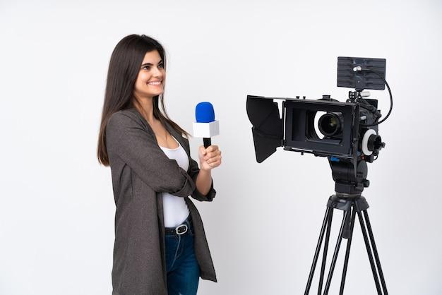 Mulher repórter segurando um microfone e relatando notícias sobre uma parede branca isolada, olhando para o lado
