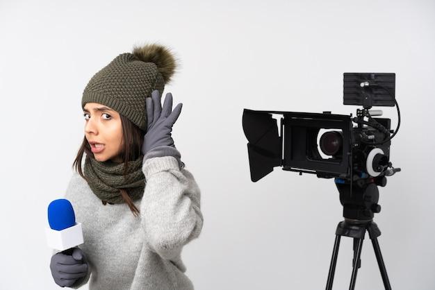 Mulher repórter segurando um microfone e relatando notícias sobre uma parede branca isolada, ouvindo algo colocando a mão no ouvido