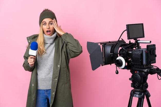 Mulher repórter segurando um microfone e relatando notícias sobre uma parede rosa isolada percebeu algo e pretende encontrar a solução