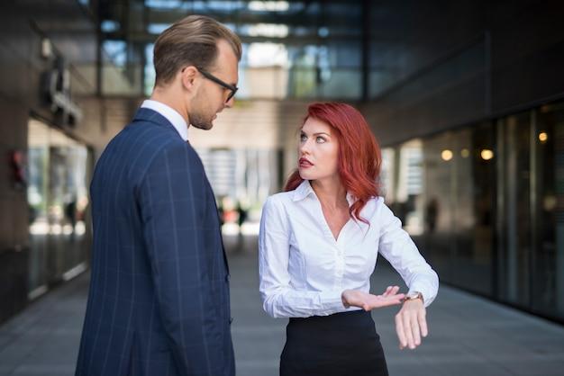 Mulher repreendendo um colega por estar atrasado