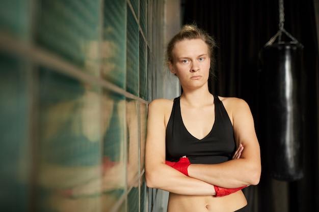 Mulher resistente, posando no ginásio